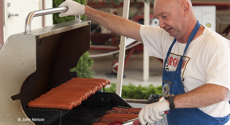 Man tending hot dogs on a gas grill