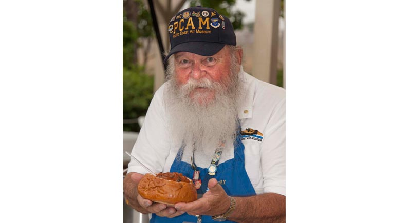 man with a beard holding a chili dog and looking like he's going to enjoy eating it