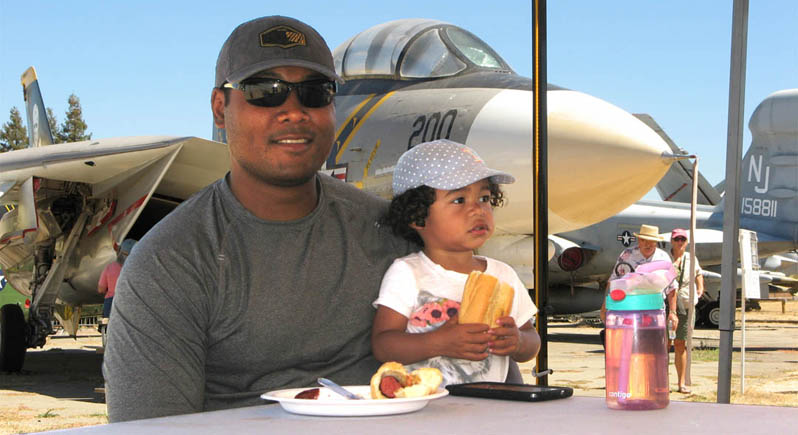 Dad holding three-year-old girl who is enjoying eating her hot dog, with F-14 Tomcat airplane in background