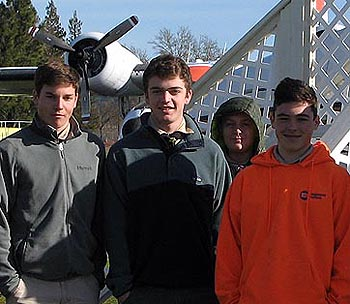 four boy scouts stand in front of an airplane