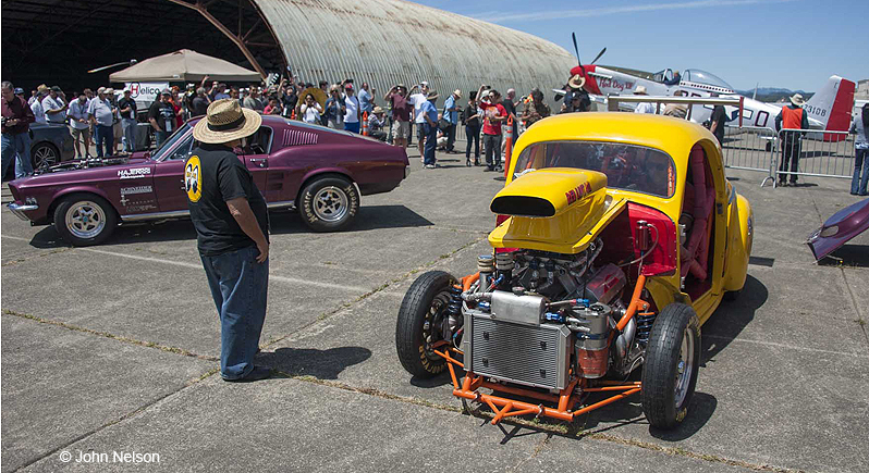 Pro-Street class 1941 Willys coiup dragster on display at a car show in front of a P-51 Mustang Fighter plane