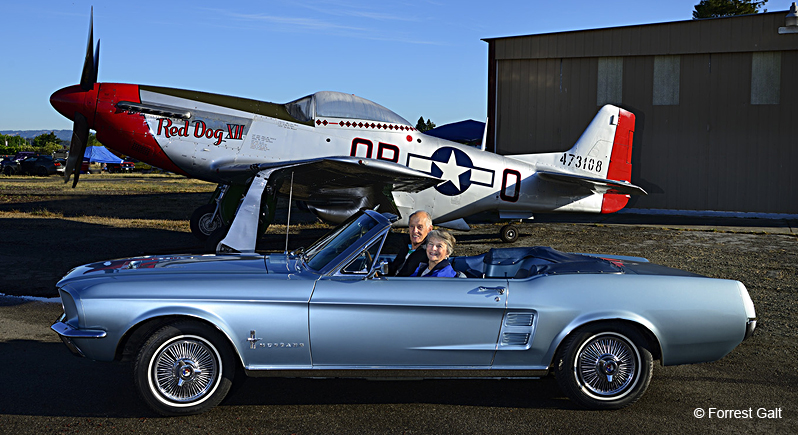 classic 1965 Ford Mustang on display at a car show in front of a P-51 Mustang fighter plane