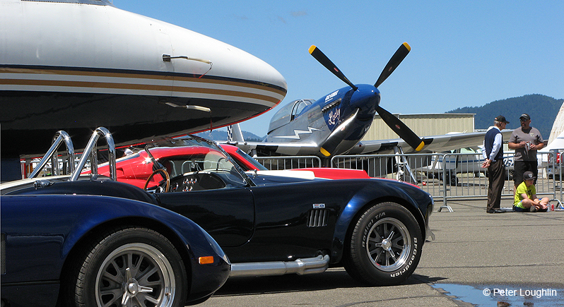 classic and muscle cars on display in front of P-51 Mustang fighter plane and a business jet at a car show