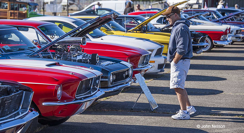man inspecting a classic muscle car with its hood open at a car show