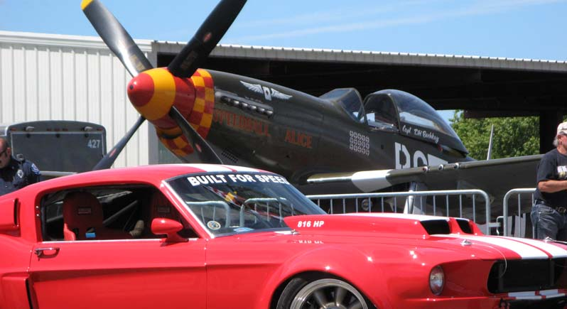 classic fastback Ford Mustang on display in front of P-51 Mustang fighter plane