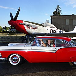 man in classic car sitting in front of P-51 Mustang fighter plane