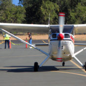 "small white and red ""taildragger"" Stinson Voyager aircraft taxiing toward the viewer."