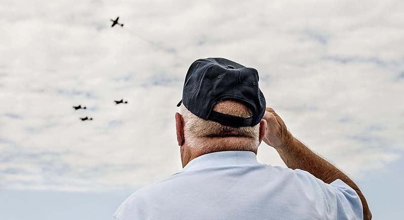 Veteran stands at attention and salutes as four warbirds fly past performing the