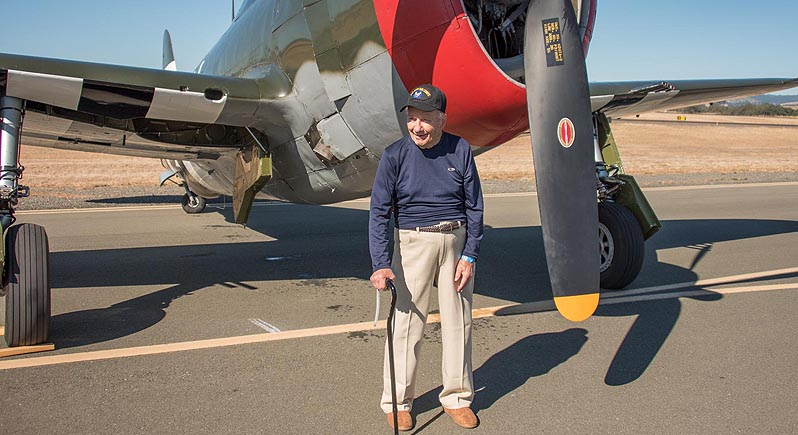 Elderly Veteran standing in front of P-47 fighter plane