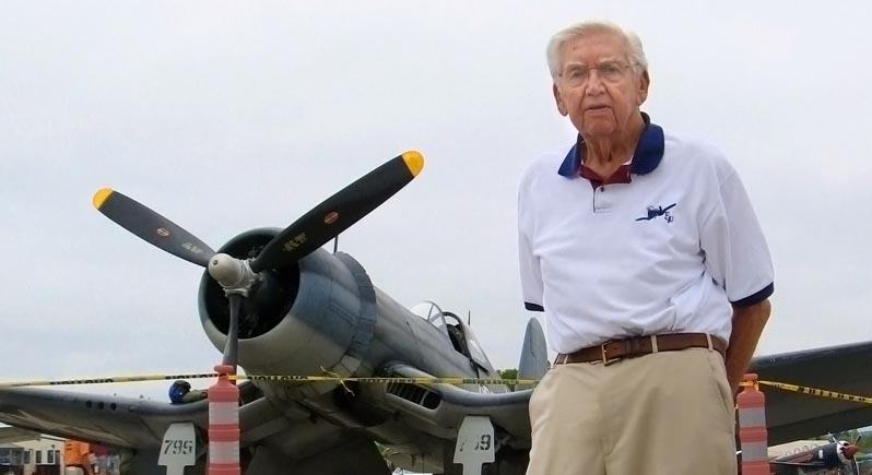 elderly WWII veteran standing in front of F4U Corsair like the one he flew in the war