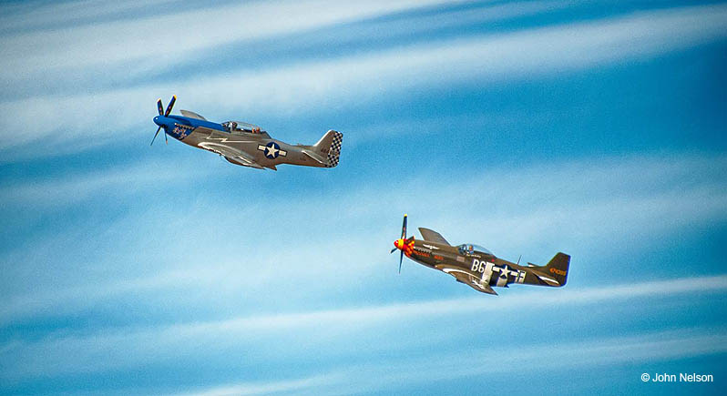 Two P-51 Mustangs fly past clouds on a blue sky. Copyright John Nelson.
