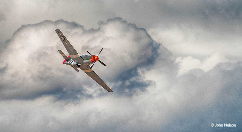 P-51 Mustang flies past dramatic clouds. Copyright John Nelson