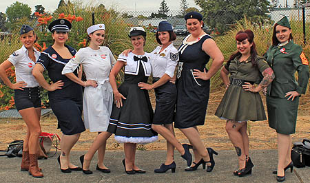 Group of glamorous women standing and posing for the camera, dressed in 1940s vintage military-themed clothing.