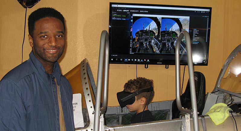 young boy with 3D headset sits in a flight simulator as his father looks on