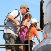 A man with young children stand atop a metal air stair and look into the cockpit of a historic jet fighter aircraft
