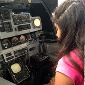 close-up photo of young girl in the cockpit of a jet fighter plane at a science fair