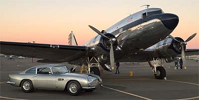 photo of vintage Aston Martin car on airport ramp at dusk next to shiny DC-3 airliner.