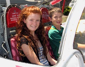 two kids sitting in the cockpit of a T-37 Tweet jet trainer aircraft