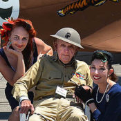 Elderly Veteran in his original World War II uniform flanked by two lovely ladies in '40s era clothing