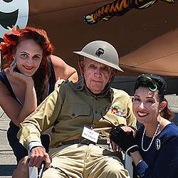 Elderly Veteran in his original World War II uniform flanked by two lovely ladies in '40s era clothing