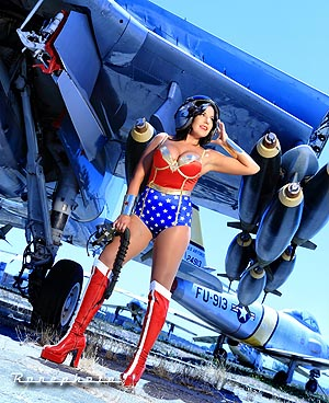 photo of woman dressed as Wonder Woman standing under the wing of a jet bomber aircraft. Copyright Ronephoto.