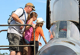 A family looks inside the cockpit of a military jet at the Pacific Coast Air Museum during Open Cockpit weekend