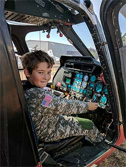 close up photo of a young boy dressed in a camouflage flight suit, sitting in the cockpit of the REACH air ambulance helicopter at the Pacific Coast Air Museum