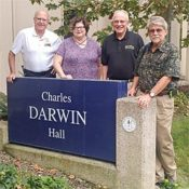 four people standing next to a sign that reads Charles Darwin Hall