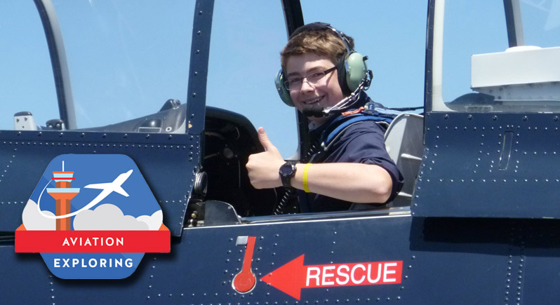 young man sitting in the back of a classic T-28 trainer giving the