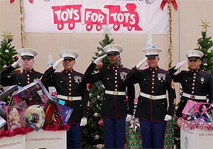 five US Marines in dress uniform saluting, in front of a Toys for Tots banner