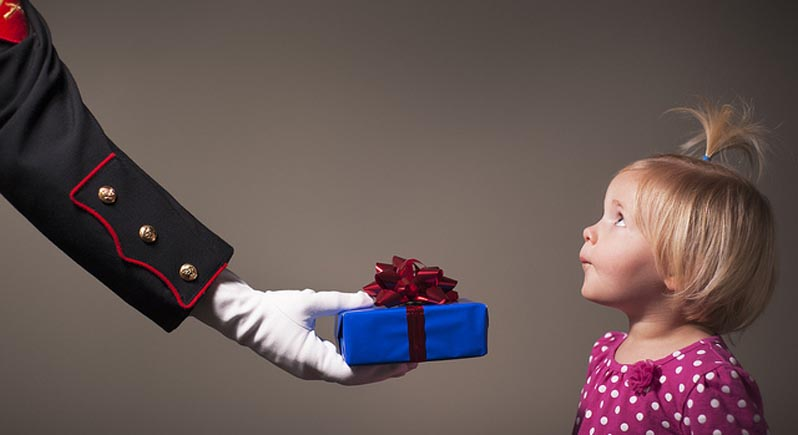 little girl accepting a gift from a US Marine