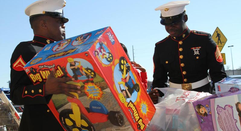 two US Marines in dress uniform distributing toys through Toys for Tots