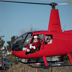 Santa Claus sitting in the cockpit of a hovering red helicopter