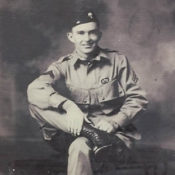 World War II Paratrooper formal portrait of a man in uniform sitting in a chair