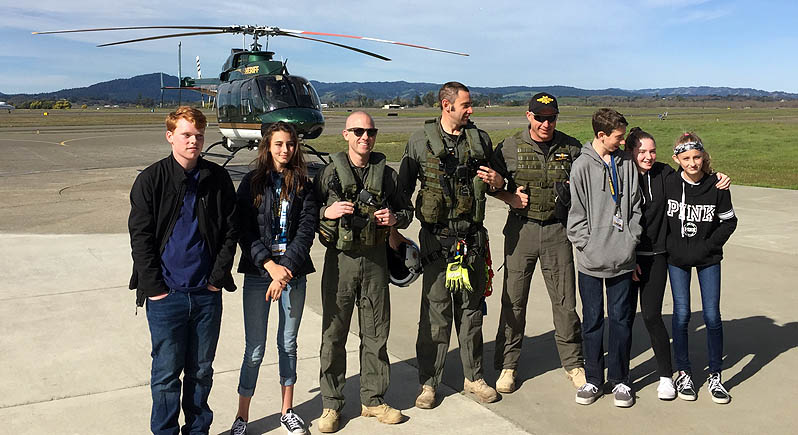 five young adults and three sheriff's department helicopter pilots and crew standing in front of a sheriff's department helicopter