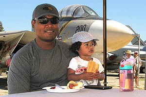 A man and his toddler daughter enjoy a hot dog at a lunch event at an air museum. There's a fighter jet behind them