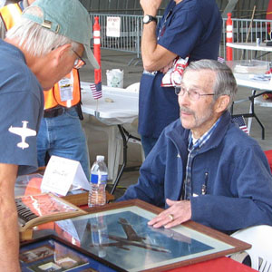 elderly veteran at a meet-and-greet event shares stories and memorabilia with a visitor