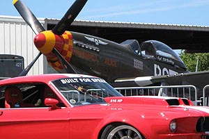 P-51 Mustang and Ford Mustang sitting near each other at a car and airplane show