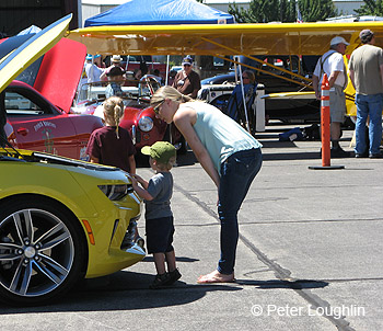 photo of woman and a small child examining a high performance Chevy Camaro. Copyright Peter Loughlin.