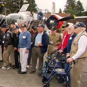 A group of elderly veterans standing near an old warplane