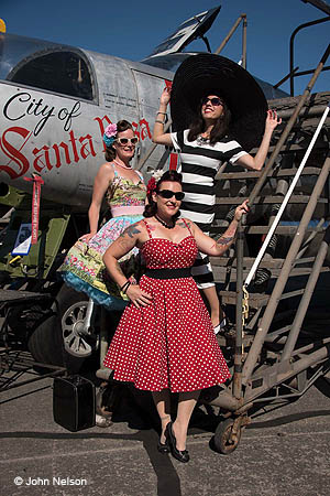 photo of three women dressed in 1940s clothing standing on the steps next to a 1940s aircraft