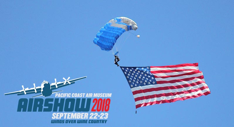 Wings of Blue skydiver trailing a United States flag, with 2018 Wings Over Wine Country Air Show logo superimposed over an empty part of the image