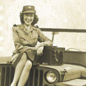 World War II era photo of a female war correspondent and photographer sitting on the hood of a Jeep