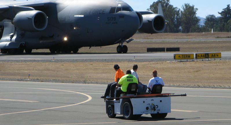 air show volunteers driving an aircraft tow tractor in foreground with a giant US Air Force transport plane taxiing in background