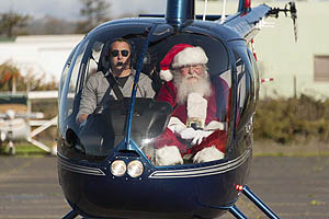 Santa Claus and pilot in a blue helicopter