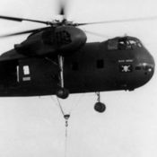 Clos-up photo of CH-37B Mojave helicopter in flight, with lifting sling underneath
