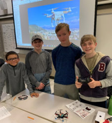 four young students standing at a table with the remote control drone they have built