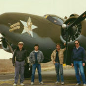Four men standing in front of a classic WWII Lockheed bomber
