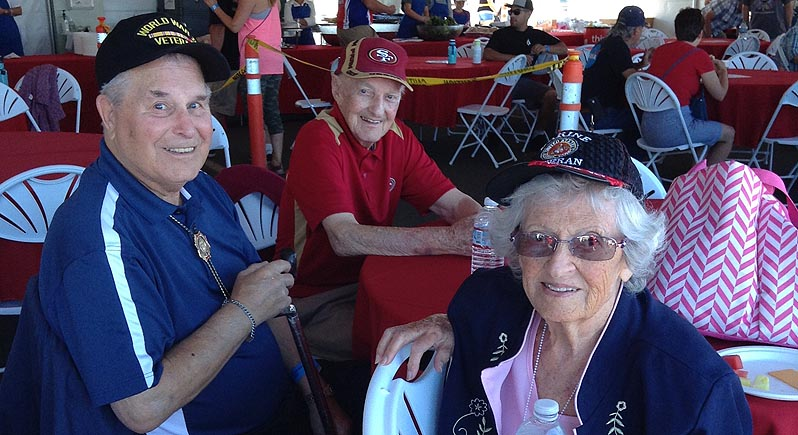photo of three elderly veterans, two men and a woman, sitting at a table at an air show