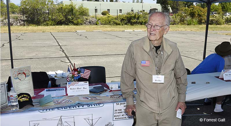 elderly veteran standing in front of ta table displaying wartime memorabilia and information about Liberty Ships